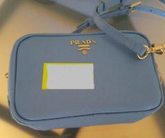 13.7.2018 Dražba dámské kabelky na rameno, modrá s nápisem Prada. Vyvolávací cena 5.000 Kč.