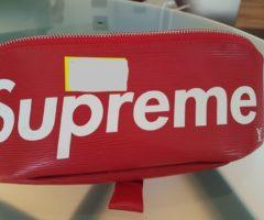 13.7.2018 Dražba sportovní kabely – ledvinka, s nápisy Louis Vuitton, Supreme, červená. Vyvolávací cena 10.000 Kč.
